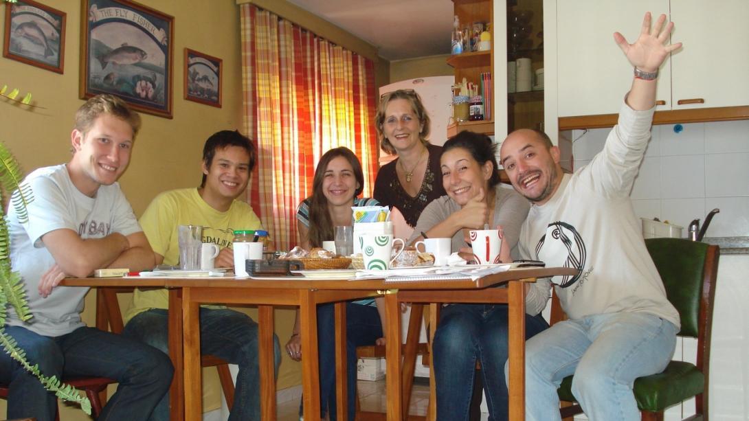 Les volontaires de Projects Abroad dégustent du thé et des gâteaux avec leur famille d'accueil en Argentine.
